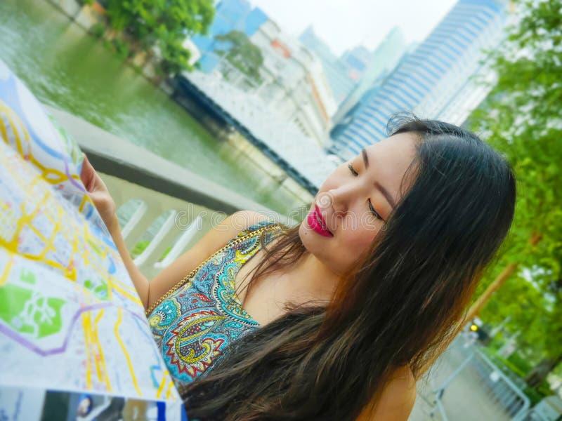 Retrato do estilo de vida da mulher coreana asiática feliz e bonita nova do turista que anda no parque da rua que olha o mapa da  fotos de stock