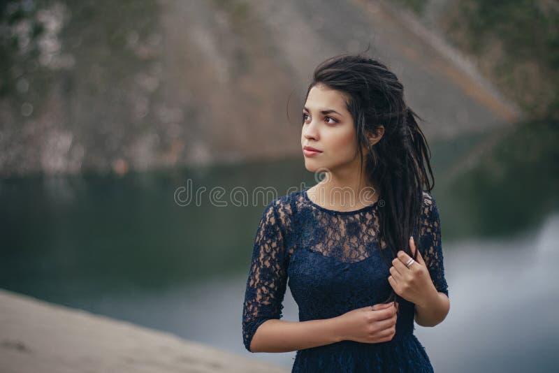 Retrato do estilo de vida de uma morena da mulher no fundo do lago na areia em um dia nebuloso Romântico, delicado, místico fotografia de stock
