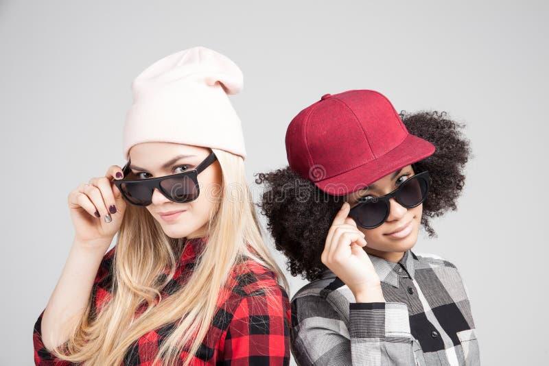 Retrato do estilo de vida do estúdio de duas meninas do moderno dos melhores amigos que vão loucas e que têm o grande tempo junto imagens de stock