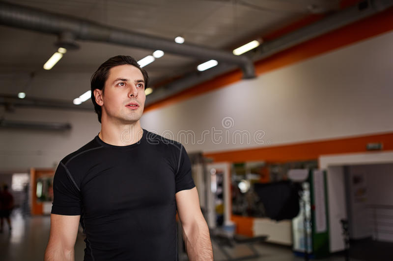 Retrato do estilo de vida do homem muscular considerável no t-shirt preto que está no gym do esporte fotos de stock