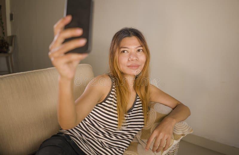 Retrato do estilo de vida do encontro indonésio asiático atrativo e relaxado novo da mulher 30s confortável com o telefone celula fotos de stock