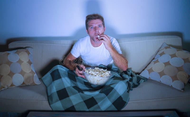 Retrato do estilo de vida do filme de observação do homem relaxado atrativo novo no assento da pipoca comer da televisão tardio n fotografia de stock royalty free