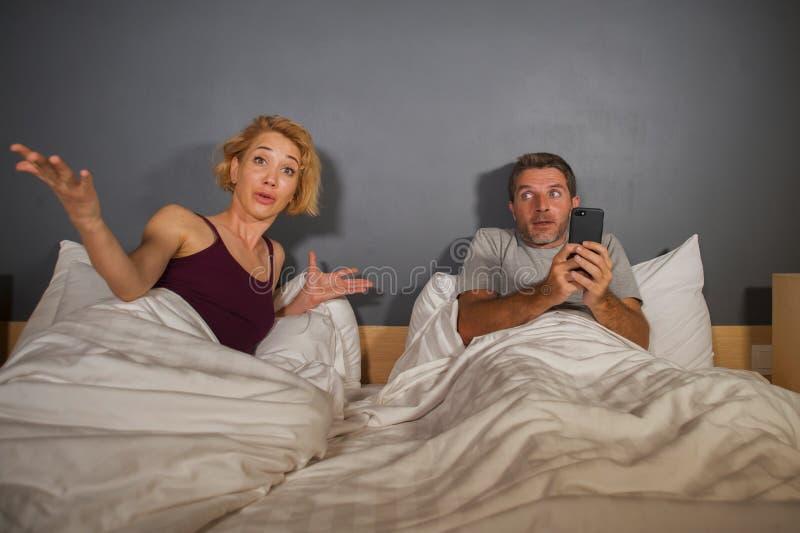 Retrato do estilo de vida do marido ou do noivo que usa o telefone celular na cama com o sentimento frustrante irritado da esposa imagens de stock royalty free