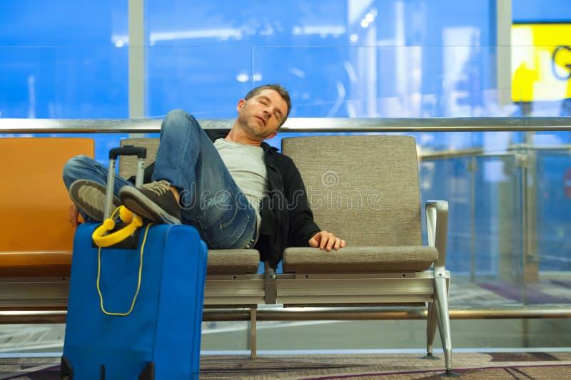 Retrato do estilo de vida no aeroporto do homem atrativo e cansado novo do turista com mala de viagem que dorme no cancelamento d fotos de stock royalty free