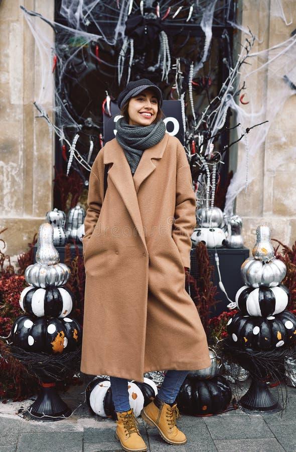 Retrato do estilo de vida do outono da mulher de sorriso bonita no revestimento bege, no lenço morno e no chapéu na rua com o Dia fotos de stock royalty free