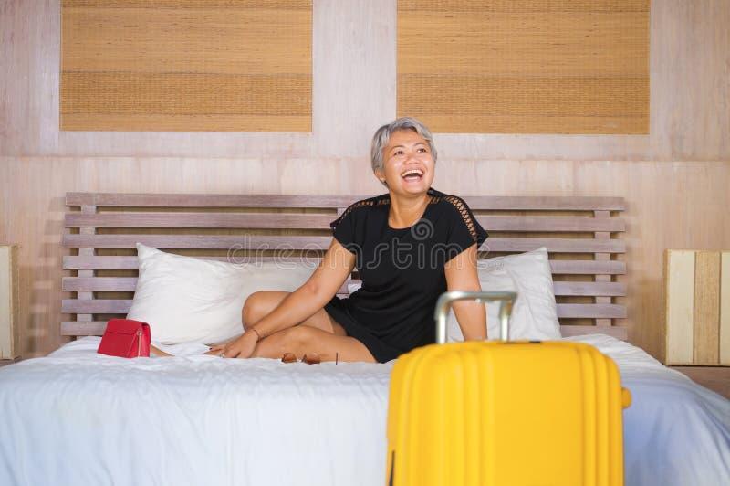 Retrato do estilo de vida de 40s feliz e atrativo à mulher asiática madura do turista 50s com o cabelo cinzento que chega na sala imagem de stock royalty free