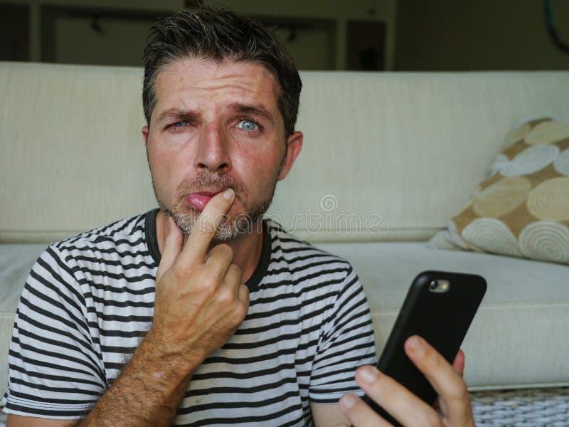 Retrato do estilo de vida do telefone celular divertido confuso e forçado novo da terra arrendada do homem que olha engraçado e p fotos de stock