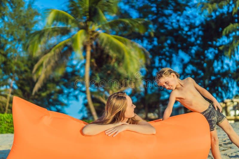 Retrato do estilo de vida do verão da mãe e do filho que sentam-se no sofá inflável alaranjado na praia da ilha tropical imagem de stock royalty free