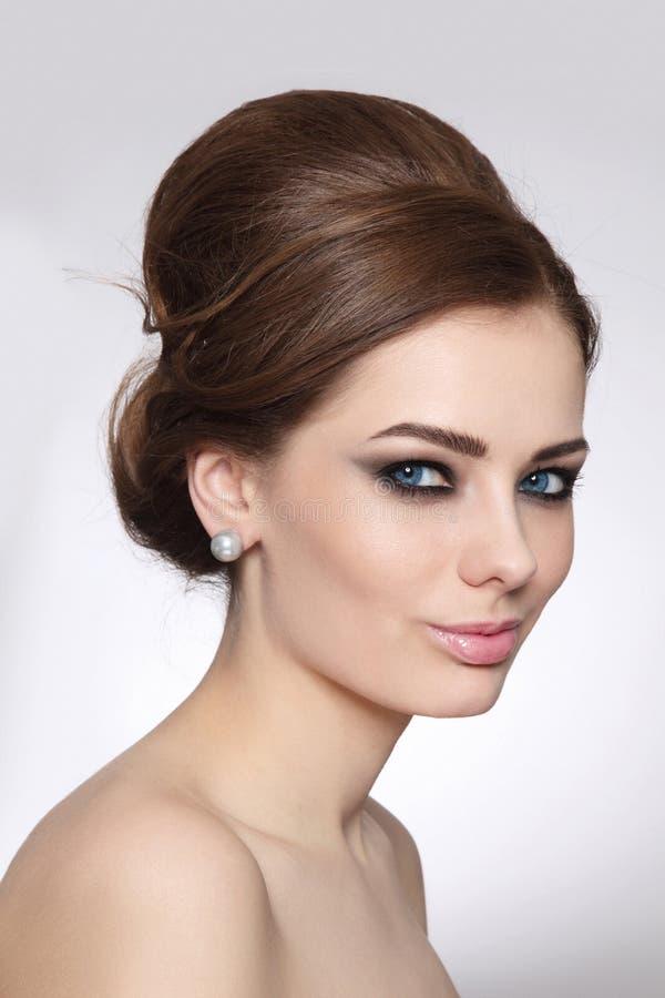 Retrato do estilo do vintage da mulher bonita com o bolo extravagante do cabelo e composição fumarento do olho imagens de stock