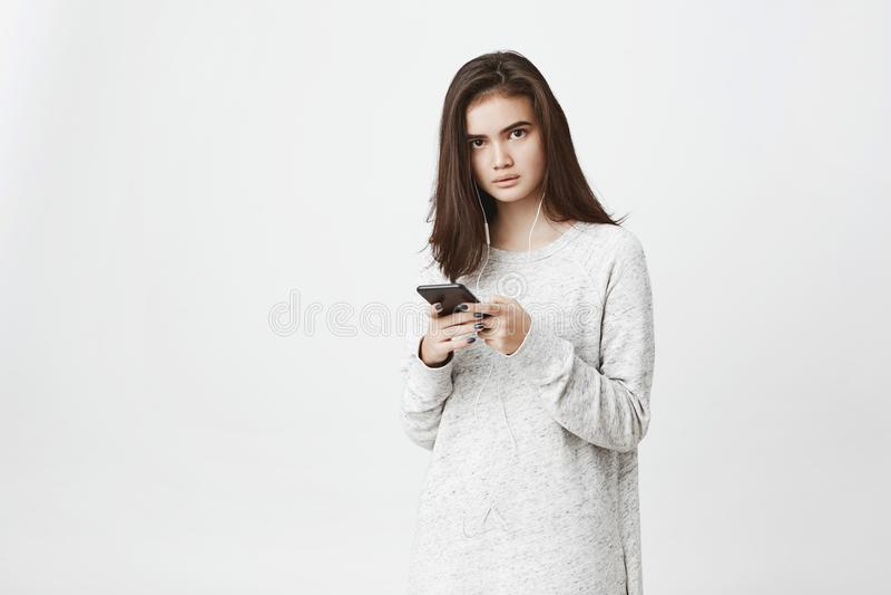 Retrato do estudante europeu bonito preocupado e frustrado, guardando o smartphone e vestindo fones de ouvido, sobre o branco imagem de stock royalty free