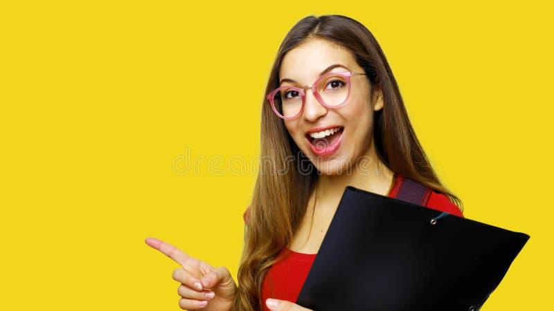 Retrato do estudante fêmea do cabelo longo bonito que veste vidros vermelhos do t-shirt e do lerdo, apontando com o indicador no  foto de stock