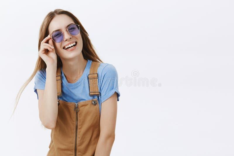 Retrato do estudante fêmea caucasiano à moda e alegre que fala apreciando o grande partido que ri felizmente estar sobre o cinza fotos de stock