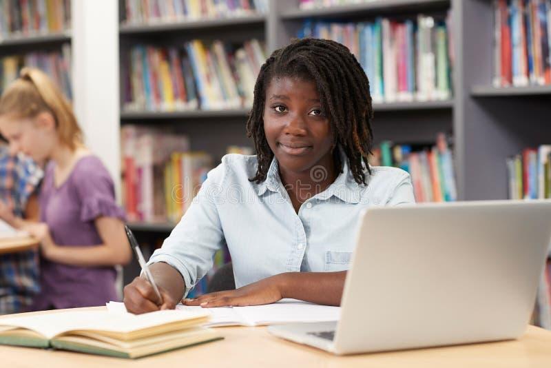 Retrato do estudante fêmea Working At Laptop da High School em Libr foto de stock