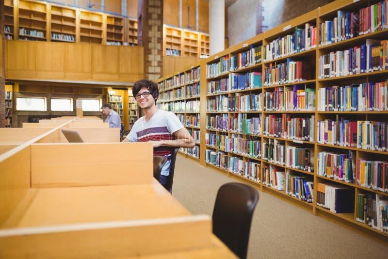 Retrato do estudante novo feliz que usa seu portátil na biblioteca imagem de stock