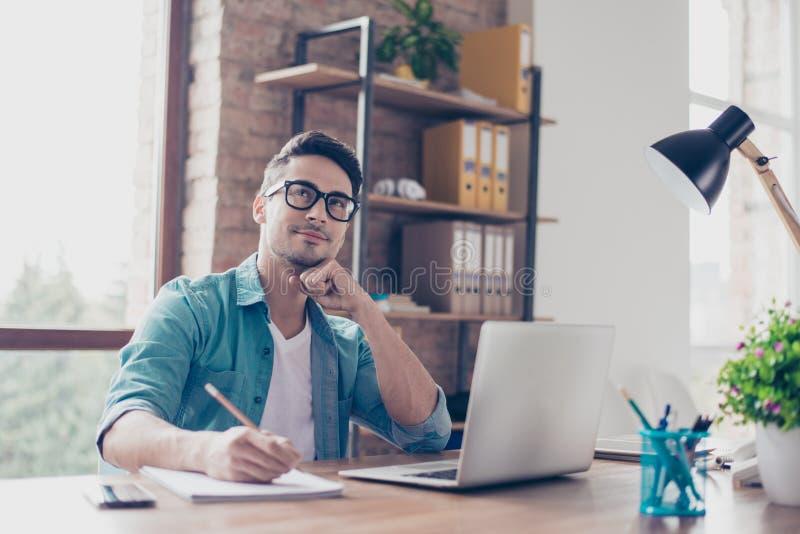 Retrato do estudante novo ocupado que senta-se na tabela no dianteiro fotografia de stock royalty free