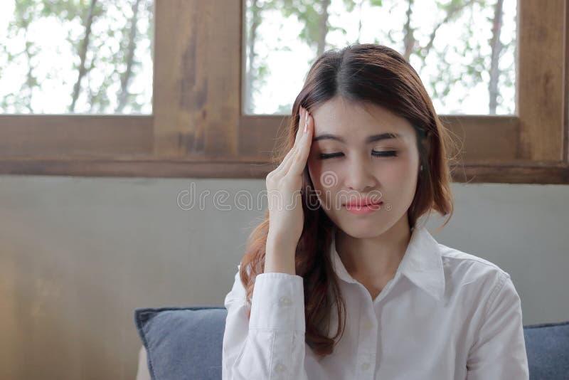 Retrato do fim asiático novo forçado da mulher seus olhos e cabeça tocante na casa imagens de stock royalty free
