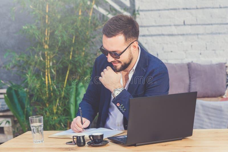 Retrato do freelancer considerável que faz anotações no café fotos de stock