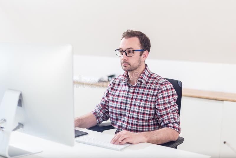 Retrato do funcionamento criativo do designer gráfico do moderno em seu computador imagem de stock