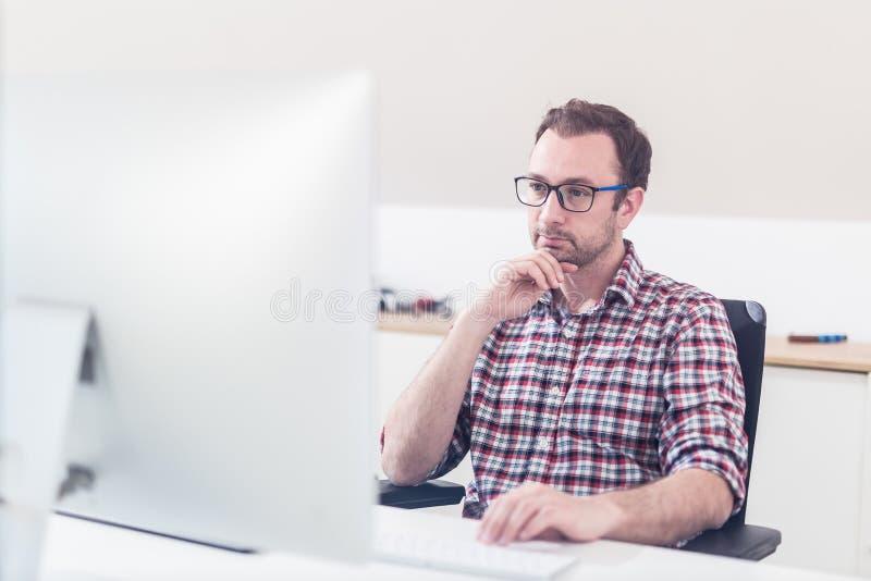 Retrato do funcionamento criativo do designer gr?fico do moderno em seu computador imagens de stock