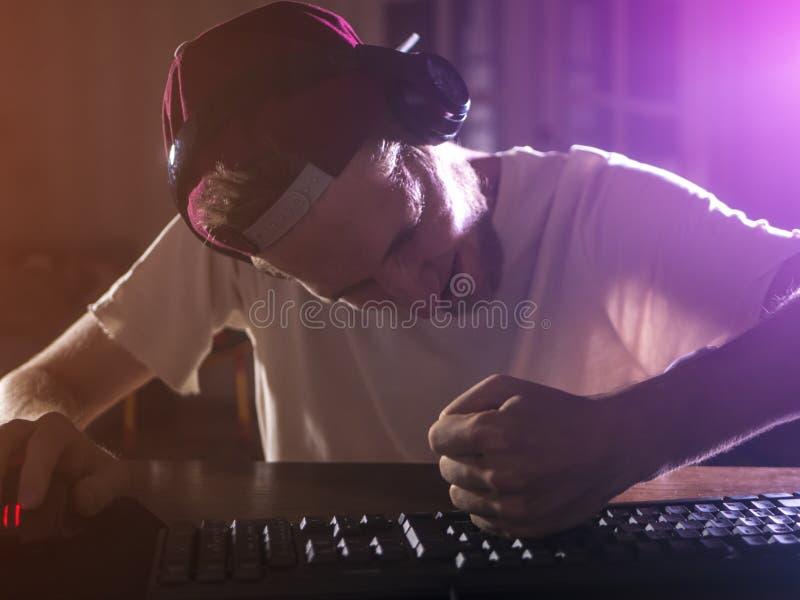 Retrato do gamer masculino farpado novo que joga o jogo de vídeo no louco louco indo da noite imagens de stock