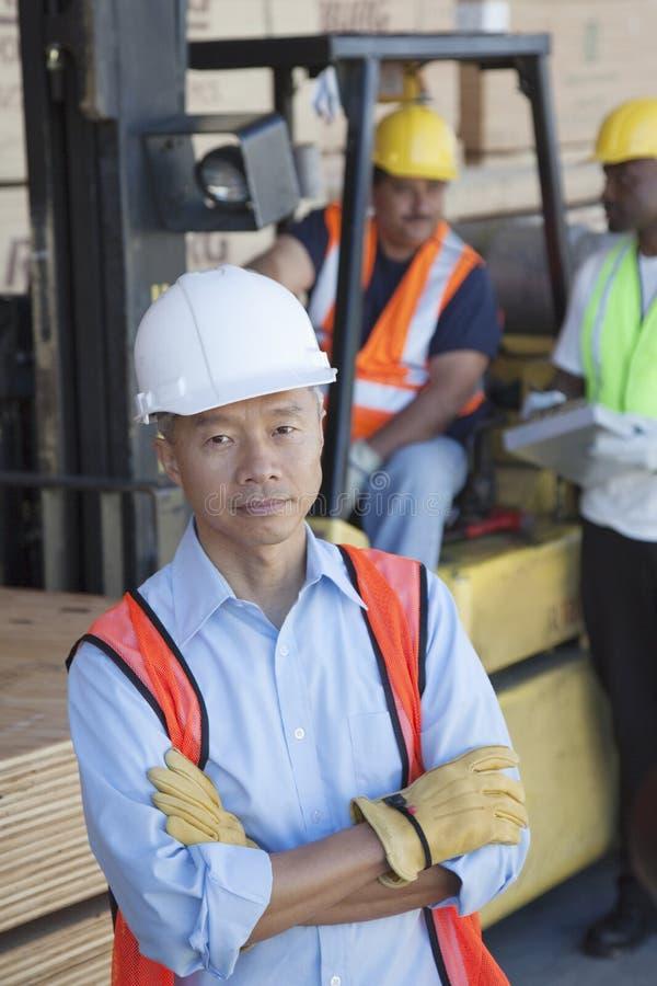 Retrato do gerente do armazém com os braços cruzados e os colegas no fundo imagem de stock royalty free