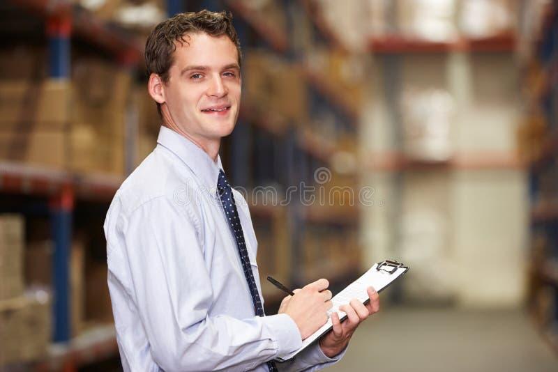 Retrato do gerente no armazém com prancheta imagem de stock