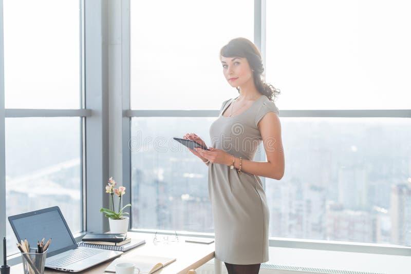 Retrato do gestor de escritório fêmea em vestir o vestido elegante, usando seu tablet pc, local de trabalho próximo estando, olha foto de stock