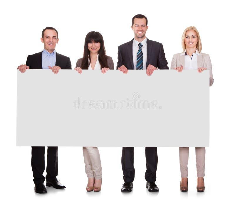 Retrato do grupo dos empresários que guarda o cartaz fotografia de stock royalty free
