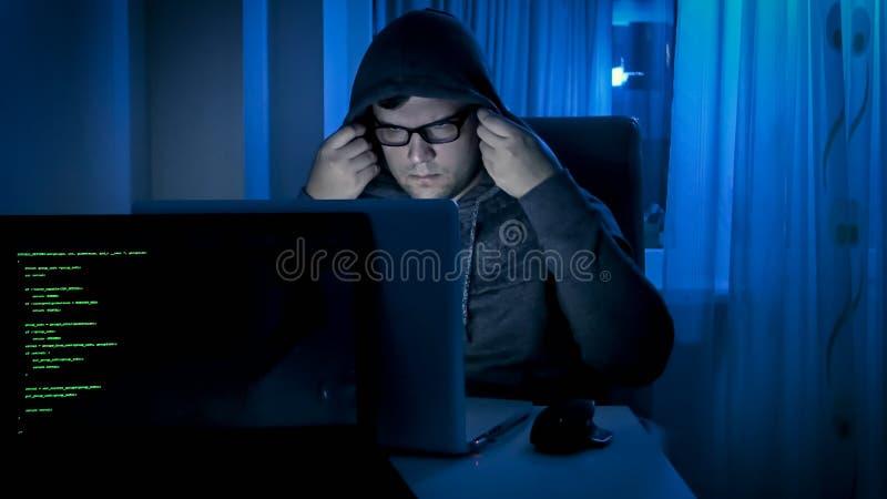 Retrato do hacker masculino que trabalha na noite e na capa vestindo na cabeça imagens de stock