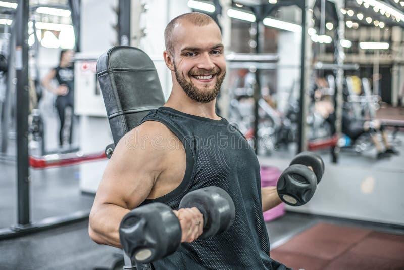 Retrato do halterofilista considerável do homem do músculo forte saudável desportivo do exercício de formação duro de sorriso fel fotos de stock