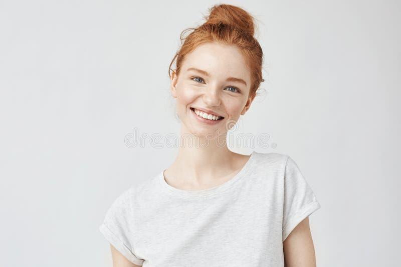 Retrato do Headshot da menina feliz do gengibre com sardas que sorri olhando a câmera Fundo branco imagens de stock royalty free