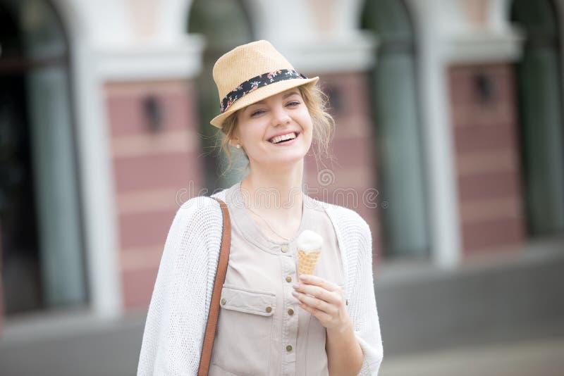 Retrato do Headshot da mulher feliz nova que come o cone de gelado dentro fotos de stock royalty free