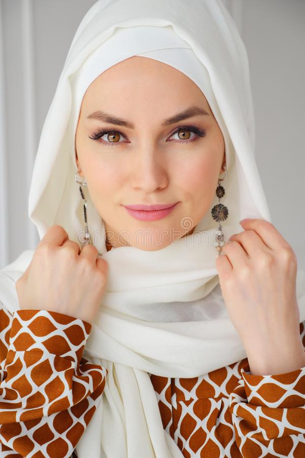 Retrato do hijab branco vestindo da mulher ?rabe mu?ulmana nova bonita que olha a c?mera fotografia de stock royalty free