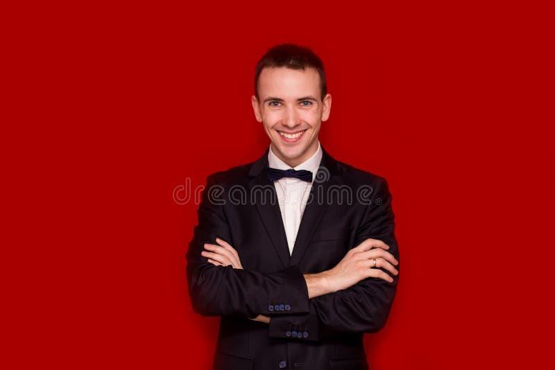 Retrato do homem à moda considerável de sorriso no terno preto elegante no fundo vermelho Estilo do negócio Imagem elegante imagens de stock royalty free