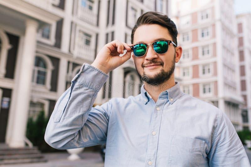 Retrato do homem à moda nos óculos de sol na rua na cidade Veste a camisa azul, barba, sorrindo à câmera foto de stock royalty free