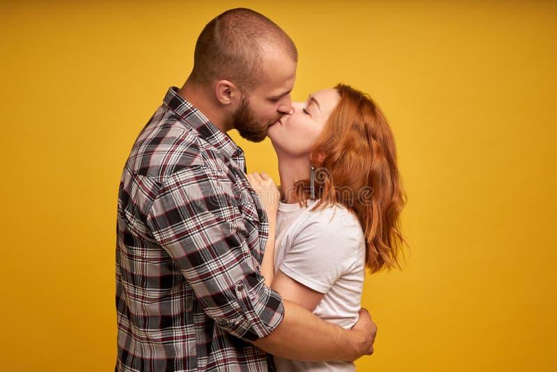 Retrato do homem adorável e da mulher dos pares vestidos na camisa quadriculado e nos t-shirt brancos que beijam e que abraçam is imagens de stock