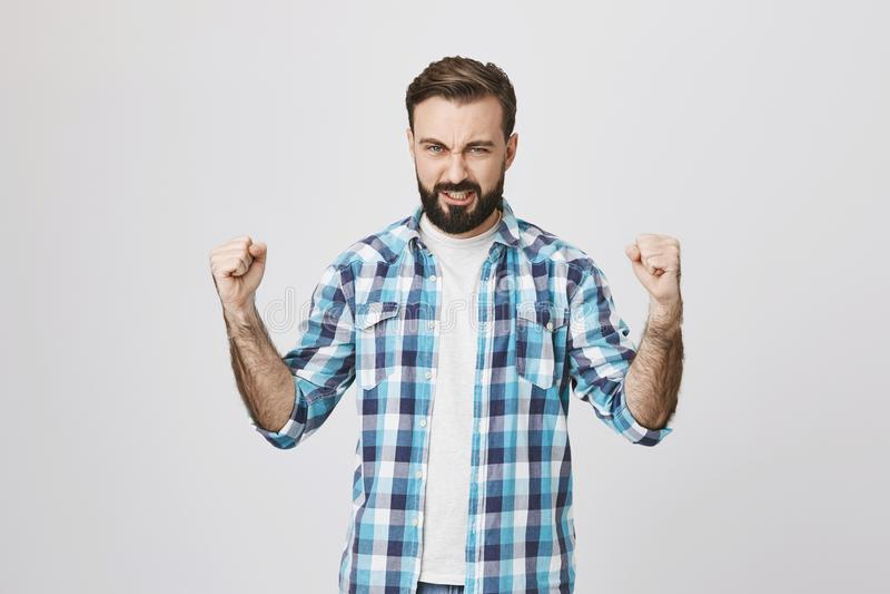 Retrato do homem adulto atlético considerável que mostra o poder e os músculos ao vestir a camisa de manta, estando sobre o cinza fotografia de stock