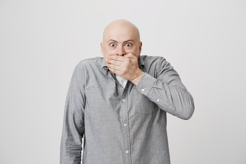 Retrato do homem adulto calvo que cobre sua boca com a mão que expressa o medo e o choque sobre o fundo branco Indivíduo em ocasi fotos de stock