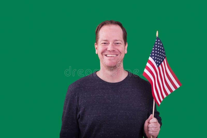 Retrato do homem adulto patriótico que guarda uma bandeira americana que sorri no contexto verde da tela imagens de stock royalty free