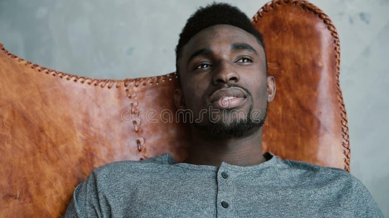 Retrato do homem africano novo que senta-se na cadeira de couro, pensando sobre algo e o sorriso O homem olha pensativamente foto de stock
