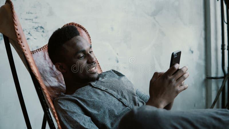 Retrato do homem africano que senta-se na cadeira, usando Smartphone O homem considerável sorri e olha fotos em seu telefone fotografia de stock royalty free