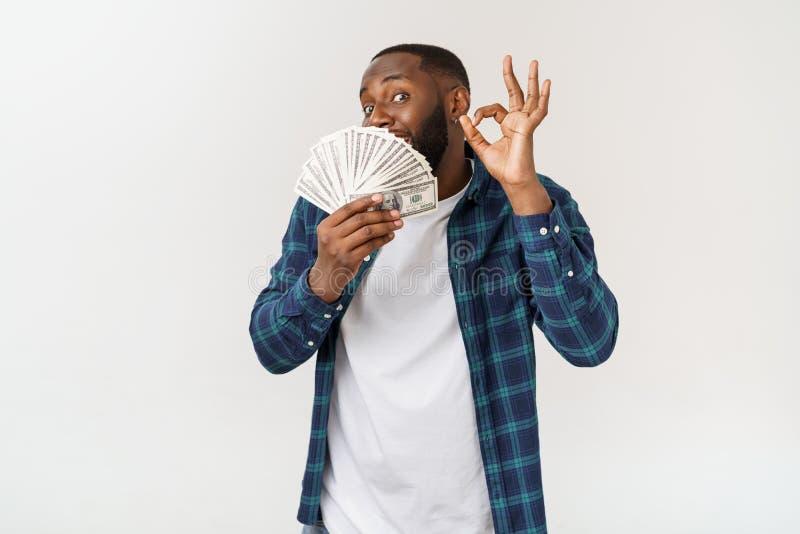 Retrato do homem afro-americano de sorriso novo da pele escura na camisa branca de t que guarda o dinheiro e que mostra o sinal d fotografia de stock royalty free