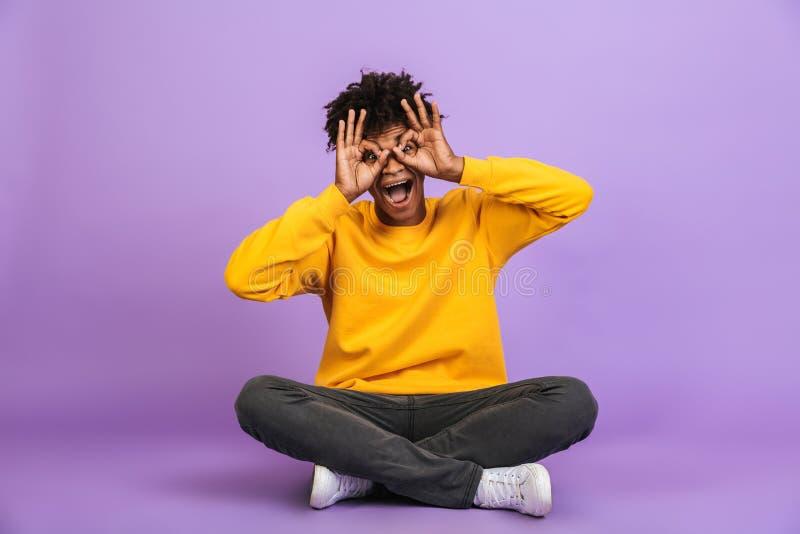 Retrato do homem afro-americano engraçado que senta-se no assoalho com pé fotos de stock