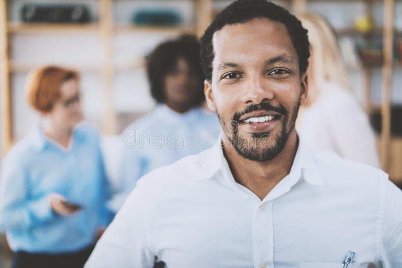 Retrato do homem afro-americano que olha e que sorri na câmera Equipe do negócio em um fundo no escritório moderno imagem de stock royalty free