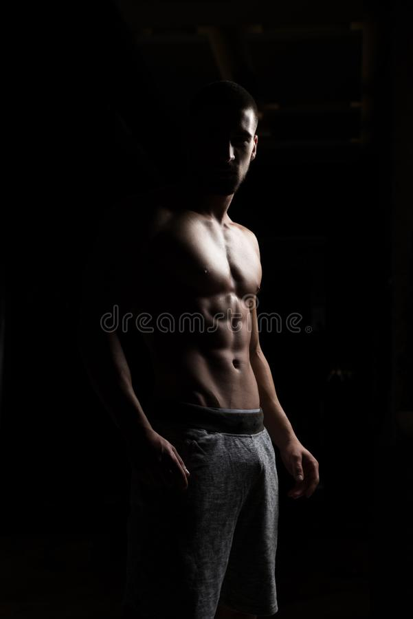 Retrato do homem do ajuste na sala escura foto de stock