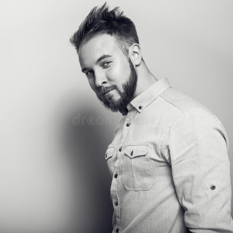 Retrato do homem amigável considerável novo na camisa brilhante foto Preto-branca do estúdio na luz - fundo cinzento imagens de stock royalty free