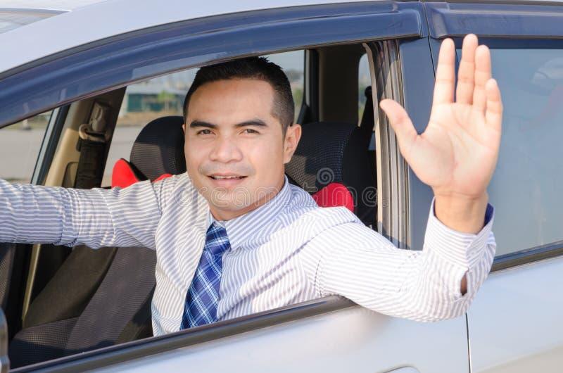 Retrato do homem asiático do sorriso que conduz uma janela de carro do opem do carro e sh imagens de stock
