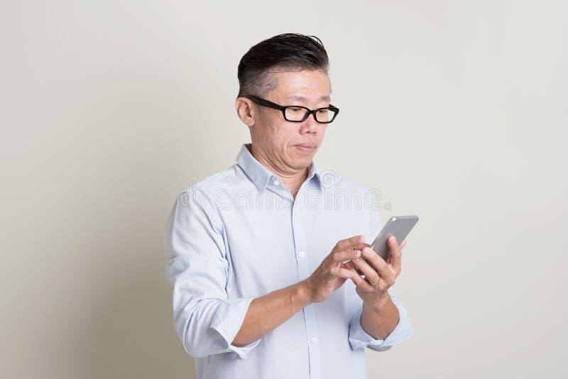 Retrato do homem asiático maduro que usa o smartphone imagem de stock