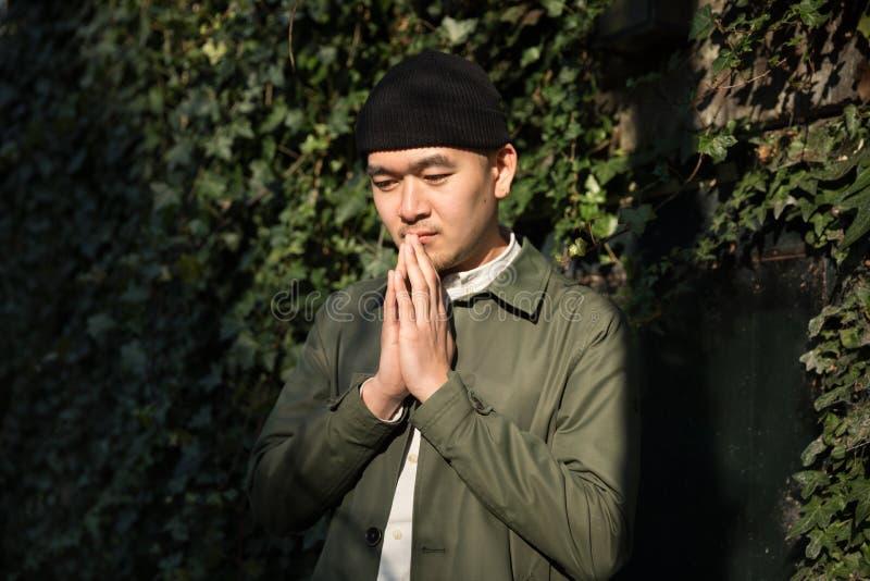 Retrato do homem asiático que reza contra ivi fundo folheado fotografia de stock royalty free