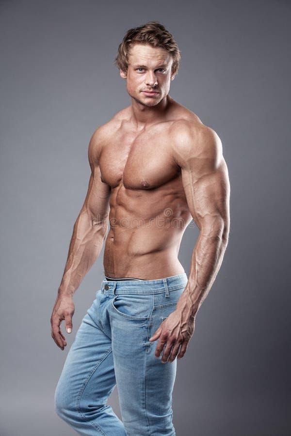 Retrato do homem atlético forte da aptidão sobre o fundo cinzento fotos de stock
